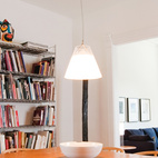 An industrial shelving unit holding Jones' library contrasts with the warm wood flooring and furniture in his dining room.