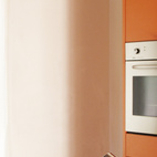 Bright orange and cobalt-blue surfaces dominate the minimalist kitchen.