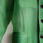 A green mesh shirt designed by Kristen Nakamura hangs from one of Liu's white walls.