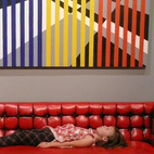A young visitor on a Milo Baughman tufted sofa in red leather with black accents, beneath Crossroads, a 2000 acrylic-on-Masonite painting by 1960s furniture designer Arthur Ellsworth, which sold on the gallery's opening night.