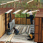 Steel trusses form the sloped roof while four separate modules create bedrooms and office space for nurses, teachers, and agriculturalists.