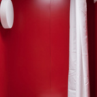 Maximizing space was of utmost importance in the 8-by-4-foot bathroom, which consists of an open shower in front of an electric composting toilet by Sun-Mar. Poteet and Hill chose a red sheet metal for the walls and laid down a non-slip epoxy flooring.  Photo by: Chris Cooper