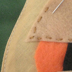 Pin his features into place, then hand-stitch them on, matching the embroidery floss to the feature.