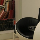 """Across from the reception desk is this computer station, tucked away in a plastic-and-leather pod like some Atomic-era invention. The hotel 'library' sits behind it, with art and design books arranged in a haphazard but artful way, available for borrowing by guests. Says Auer: """"I always loved the comic strip 'Gaston Lagaffe.' The character's books are arranged like this in storage piles forming caves. I took up this idea.""""Don't miss a word of Dwell! Download our  FREE app from iTunes, friend us on Facebook, or follow us on Twitter!"""