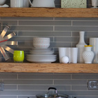 """Dishes rest atop a shelf made from a type of textured lumber typically used for framing. The horizontal tile behind the shelf echoes the pattern and proportion of the bricks used in the hearth.Michelle and Cameron did nearly all of the work themselves, which was often a learning experience. """"We had to be willing to roll with the punches. A dimple in the concrete counter isn't a mistake—it adds character,"""" she says. """"When people visit our house it tells them a story, and I think we all respond to that."""""""