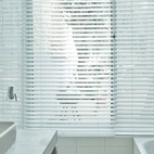 The master bath is a clean and spare space, a mixture of white and concrete.  Courtesy of: Copyright:Tobias Hochstein