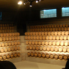 """A collection of 2,500 barrels are inside the """"Barriquerie"""", each holding wine that will age for up to 20 months. Piano calls this space the winery's """"secret soul."""" """"The magic [of the space] comes from these 2,500 barrels that watch you like huge eyes,"""" Piano said. At center in the ceiling is the skylight that directs a central beam to the middle of the floor. In the background are windows to the surrounding chamber that holds the steel vats that process the grapes. Photo by Amanda Dameron.  Photo by: Amanda Dameron"""