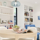 Opposite the kitchen is a dining area and living room, which can be partitioned off with a set of folding doors. The dining table is from Ikea and the chandelier is from Niche Modern.