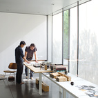"""Atherton and Keener review architectural drawings in their """"living room,"""" which also serves as a work studio and performance space."""