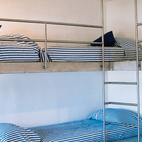 The rounded steel guardrails on the kids' bunk beds are meant to inspire fantasies of nautical adventures.  Photo by: Paco Perez / Alluro