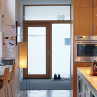 The kitchen, which gets light from three sides, welcomes guests into the house.  Photo by: Lorne Bridgman