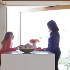 Carole and granddaughter Allison—–silhouetted against a glass door that pivots open to the front garden—–plot how they'll prepare the family's next meal at the kitchen island.  Photo by: Shawn Records