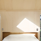 Plywood is used throughout the interior of this small, barn-inspired house in an apple orchard in Havelock North, New Zealand. There's Gaboon plywood below the datum and Italian poplar above it, used on everything from the walls and ceiling to the bench and cabinets in the kitchen to the wardrobes and shelving. The mezzanine bedroom sits beneath the off-center apex of the pyramid roof, with a view over the orchard. Photo by Patrick Reynolds.  Photo by: Patrick Reynolds