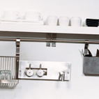 """Mandi Rafaty's girlfriend, Yoly Guerra, unpacks groceries in preparation for dinner. The kitchen cabinets are off-the-shelf models from IKEA, and all knives are stored on a space-saving magnetic hanging holder on the wall. Two floating, open shelves above the Tag Front cast-concrete sink and Frigidaire dishwasher act as home base for plates and dishes, while a convection oven by Sharp, Turbo Air commercial-grade refrigerator, and two glass cabinets finish off the kitchen. """"It's all about creating these setups that don't visually make the space feel smaller than it already is,"""" Mandi says.  Photo by: Baerbel Schmidt"""