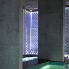 """An interplay of geometries in what Khanna calls """"the belly of the building."""" Uplights create new angles of light, raw concrete retains a rough edge and square pool tiles add texture and color while offsetting the perforated circles. The dropped ceiling at right is part of a small balcony overlooking the pools; beneath it is a sitting area."""