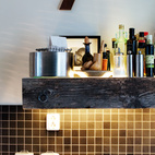 The shelf over the sink is made from wood scraps from an old jetty. It's lined with glass on the top and bottom, to better reflect light and show off the objects Schonning has arranged on it. Photo by Per Magnus Persson.  Courtesy of Copyright Per Magnus Persson.