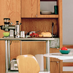 Even in the Stonorovs' tiny first-floor room, the curse of the kitchen as the inevitable gathering place lives on—–though the two-foot space between the sink and metal island is less than ideal for the family of three and their blue heeler, Oscar.