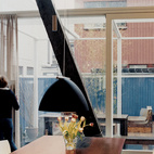 The suspended living room's scaly belly doesn't detract from the unfussy kitchen and dining area. A recycled Berlage-era table base (with a new tabletop), a deep blue lamp, and Arper chairs add to the maritime feel of the house.