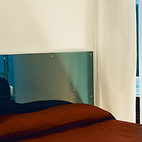 The glass platform bed is backed by a headboard of two sheets of lucite embedded with aquamarine wool from Maharam. Hanging pillow-side, electroluminescent draperies glow in the dark.