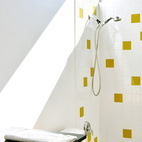 """Light floods the second-floor bath, which is housed within a birch-ply """"box"""" also containing storage. The water is heated by a tankless, on-demand unit from Rinnai. The architects continued the tile motif for the bath downstairs; the honey-colored tiles are from Dal-Tile. The lamp is by Kathleen Ash of Studio K Glass.  Courtesy of ©2009 Patrick Y. Wong."""