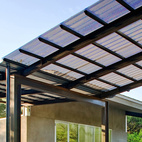 """After the home was completed, Wong asked for the carport addition. """"I handed Jay two books: one on Alexander Calder's mobiles, and one on insects,"""" says Wong. The result was a soaring, winglike steel, aluminum and Galvalume structure fabricated by the architects that gives additional protection from the sun, provides a smoother transition from exterior to interior, and allows clients and other visitors a covered space under which to park.  Courtesy of ©2009 Patrick Y. Wong Copyright Case # 1-266025680 Filed October 27, 2009."""
