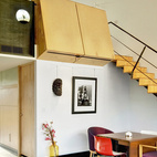 Wong's photographs dot the living area/studio; a painting by Li is at right. The architects put in a black concrete floor and designed the overhead birch-ply blocks, which double as bookcases for the upstairs sleeping loft. Accompanying a Saarinen Tulip table is a loveseat from Palazetti. Architect Michael Graves designed the chair with the circular cutout; opposite it is one designed by architect Jim Wallace for Novikoff, and the pair of red-and-white Catifa chairs are from Arper. The stair is made from Radiata plywood.  Courtesy of ©2009 Patrick Y. Wong Copyright Case # 1-266025680 Filed October 27, 2009.
