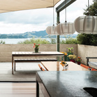 The north-facing doors slide completely away to open the house to the outdoors, offering an uninterrupted view of the water. The pendant lights over the table are from Iko Iko.  Photo by: Matthew WilliamsCourtesy of: matthew williams