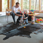 On a lakeside plot outside Toronto, four friends forge a new kind of vacation house. The architect helps his son Soren construct a TinkerToy tower. The cowhide rug is from Perfect Leather Goods, and the Wassily Chair is by Marcel Breuer for Knoll. Photo by Lorne Bridgman.  Photo by: Lorne Bridgman