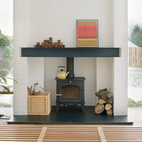 In the living room, a Nelson bench doubles as a coffee table, and a wood-burning stove from Cleanburn Stoves keeps the space warm.  Courtesy of Andrew Meredith 2007.