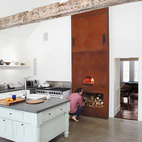 In the kitchen of Floating Farmhouse in Eldred, New York, a custom-built wood-fired oven extends up to the ceiling, accentuating its steep pitch. Photo by Mark Mahaney.  Photo by: Mark Mahaney