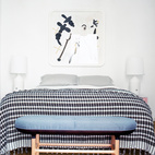 In keeping with Jaime Hayon's goal of creating a serene and airy home, the master bedroom and sticks to a mostly neutral palette of whites and grays. The bench by the bed is a custom piece designed by Hayon and his wife Nienke Klunder and fabricated by their carpenter friend Josep Joffre. Photo by Nienke Klunder.  Photo by: Nienke Klunder