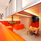 """The kitchen and dining area and is surrounded by orange steps that function as seating. The dugout allows for a second level used for the bedrooms, which are housed in a polycarbonate """"lightbox.""""  Courtesy of                                                       ."""