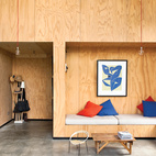 """The exterior of the Popadich residence on Auckland's North Shore is modeled after boat storage sheds, while the interior is outfitted with industrial concrete and ply. """"We decided to line the interior in exposed plywood sheets [to save money],"""" says Davor Popadich, a director at Pattersons Architects in Auckland, New Zealand. """"On paper, plasterboard seemed cheaper, but then we realized it would cost money to plaster and paint it, which pushed the overall cost up. And the builders liked that, because they got to show off their workmanship, which is usually covered up by plaster and paint."""" Photo by Simon Devitt.  Photo by: Simon DevittCourtesy of: © 2011 Simon Devitt"""