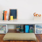 Bovee uses the small desk at the foot of the couple's bed for freelance writing projects.