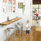 A wall-mounted oak bar is where Siminovich and Kerner drop their keys, pound away on their laptops, and occasionally eat a quick meal with Matilda, their two-year-old daughter.  Photo by: Daniel HennessyCourtesy of: ©2011 DANIEL HENNESSY PHOTOGRAPHY, LLC