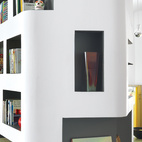 H2O Architectes used curvy cutouts in the space's central column to draw the eye around its corners. A clever recessed cupboard conceals the TV screen. Comics, clearly, are everywhere.