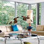 The living room of the Goddard-Mandolene residence features vintage furnishings by Harry Bertoia, Paul McCobb, and others, and overlooks its heavily wooded site, which adjoins a protected watershed. Goddard and Mandolene replaced the original tile floor with a glossy coat of resin and restored the original ceiling. Designed by architect Arthur Witthoefft in 1957, the home eventually fell into disrepair. See the striking before and after here.  Photo by: Jason Schmidt