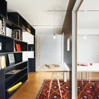 A Tokyo architect's shape-shifting apartment takes a holistic approach to live/work style. Shibata made the 10-person dining table using $130 sawhorse legs from Maruki Wood Products Company topped with a sheet of birch plywood. A hole in the sliding wall fits over the table, enabling it to be used in both the library and the meeting room. A movable wall clad in wainscoting on one side slides along tracks in the dining-room ceiling, dividing the room into a meeting space and a library. Photo by Ryohei Hamada.  Photo by: Ryohei Hamada