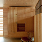 The lower-level sleeping area boasts a plywood wardrobe, Eames LCW, and Eames plywood folding screen.