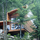This shot looks north from the lake edge and shows the raised elevation and transition to the existing cabin.