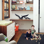 In a Missouri farmhouse, built-in shelves and a changing table accommodate future generations. Governed by the principle of utility, every space in this home is multipurpose, with nothing separating the living room from the playroom. Photo by: Joe Pugliese.  Photo by: Joe Pugliese