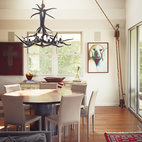 Paul painted the antler chandelier in the dining room, purchased from a friend in Alaska, glossy black. The pulley, selected from Paul's growing collection, is fully functional. The custom-built dining table is ringed by Folio Leather side chairs  from Crate & Barrel.