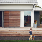 Link Catlett and Butters, the dog, stroll alongside their home's namesake wraparound porch, made of Brazilian ipe. Rolling slatted doors screen  the living room windows, providing shade on sunny days.