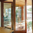 Easy Transitions To visually connect the kitchen with the outdoor covered patio, the architects installed a cedar ceiling that flows from interior to exterior, peppered with an uninterrupted grid of Iside 2 puck lights from Leucos USA. Bifold accordion doors by Sierra Pacific open all the way, allowing the Zuckermans' large dinner parties to spill outside.leucosusa.comsierrapacificwindows.com  Courtesy of ©Lincoln Barbour - All Rights Reserved.