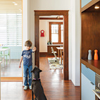 To help define the kitchen, the architects designed a wall of storage with cubbies on one side and a pantry with appliances on the other. Colorful doors add a playful touch, and DP3 Series cabinet pulls from Doug Mockett & Company keep the surfaces streamlined.  Courtesy of ©Lincoln Barbour - All Rights Reserved.
