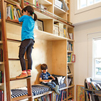 """A former closet was transformed into a double-height library, complete with a reading nook and a rolling ladder from Spiral Stairs of America. """"That's my favorite part of the house,"""" says Dan. """"When I see Stella reaching for a book, there's nothing better.""""  Courtesy of ©Lincoln Barbour - All Rights Reserved."""