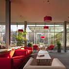 """In The Living Room, a meeting place in the hotel, Piano chose a vibrant red because simply because he loves the color. """"The material choices were made in mind of the levitation of the volume and to welcome the public with informal activities,"""" he said.  Courtesy of: Nic Lehoux / Renzo Piano Building Workshop"""