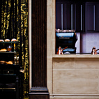 Even in the kitchen to dining room passthrough, the details are just right: a La Marzocco espresso machine and a peek of vibrant purple set inside a travertine windowbox.
