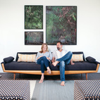 Gabbert and Avery relax on a vintage sofa in their living room beneath large-format photos of juniper bushes by Maegan Hill-Carroll.  Photo by: Catherine Ledner