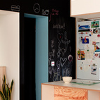 A coat of chalkboard paint can keep children and adults alike entertained for hours, providing a blank canvas for any creative endeavors. In this Bratislava apartment, a kitchen wall serves as a gallery for childrens' drawings and a notepad for their parents' shopping lists.